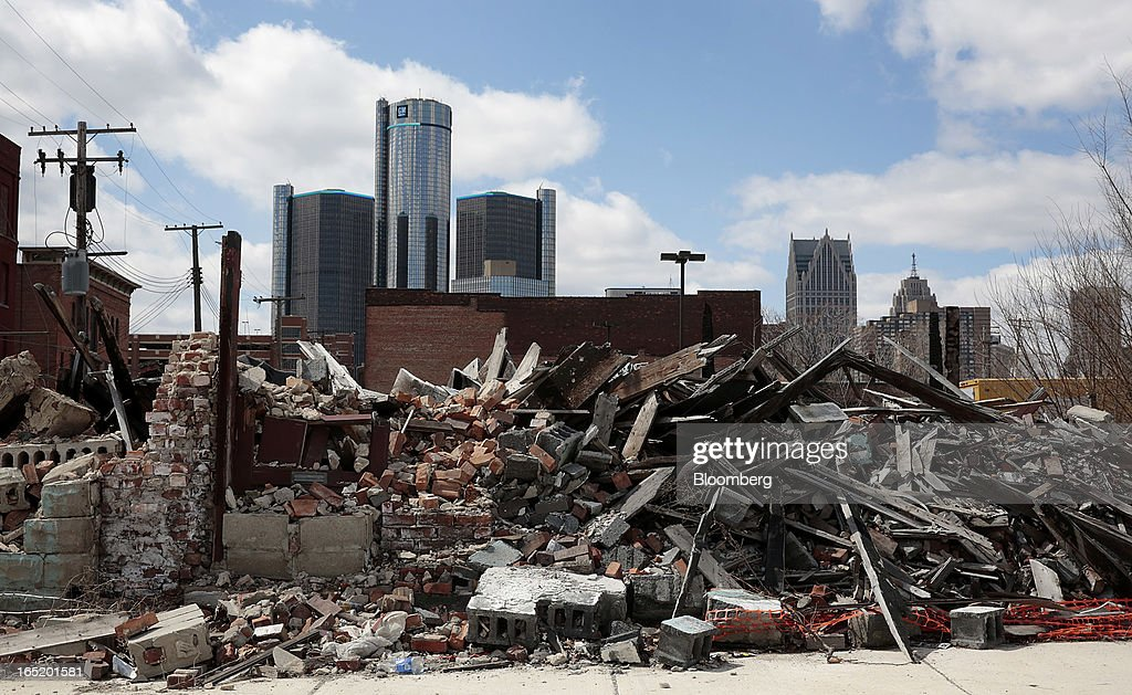 The General Motors Co. (GM) headquarters building is seen in the distance past a past a pile of debris in Detroit, Michigan, U.S., on Monday, April 1, 2013. U.S. automakers are surging, while Detroit is in such distress that it's being taken over by the state of Michigan today. Photographer: Jeff Kowalsky/Bloomberg via Getty Images