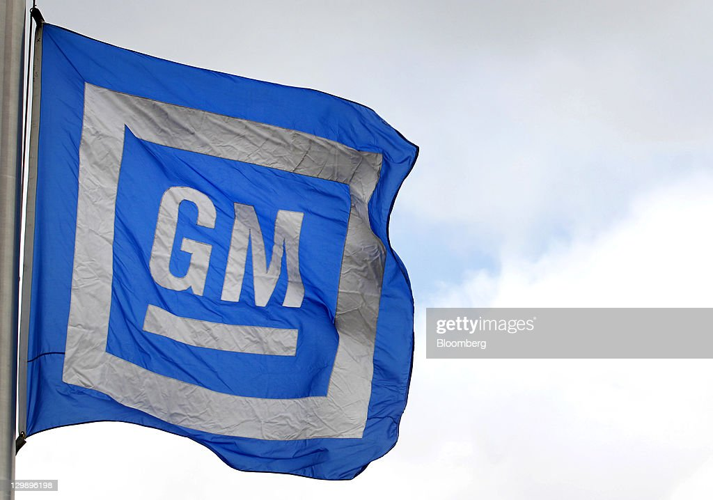 The General Motors Co. (GM) logo is displayed on a flag flying outside of the company's transmission plant in Warren, Michigan, U.S., on Friday, Oct. 21, 2011. General Motors said they will invest $325 million in tools and equipment to support production of future electric vehicle components, creating or retaining 418 jobs. Photographer: Jeff Kowalsky/Bloomberg via Getty Images