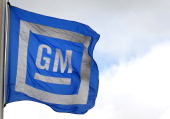 The General Motors Co logo is displayed on a flag flying outside of the company's transmission plant in Warren Michigan US on Friday Oct 21 2011...