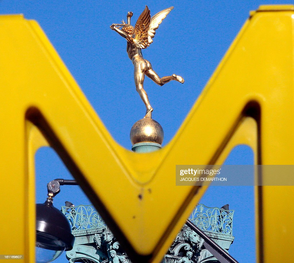 The 'genie de la Bastille' statue, situated ontop of a column in Paris' Bastille square, is pictured through a Metro sign on February 8, 2013 in Paris.