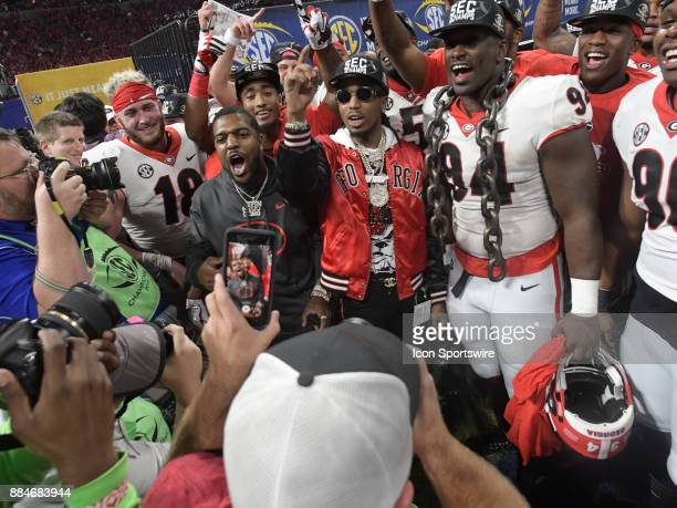 The Georgia Bulldogs celebrate with Hip Hop artist Quavo during the SEC Championship game between the Georgia Bulldogs and the Auburn Tigers on...