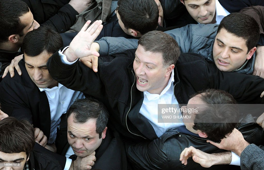 The Georgian capital Tbilisi mayor, Gigi Ugulava (C), gestures as he scuffles with protesters in Tbilisi , on February 8, 2013. An angry crowd of around 300 protesters aimed today punches and kicks at the mayor of Tbilisi and several lawmakers from President Mikheil Saakashvili's party in the Georgian capital, hours before the president was to give his annual state of the nation address. AFP PHOTO / VANO SHLAMOV