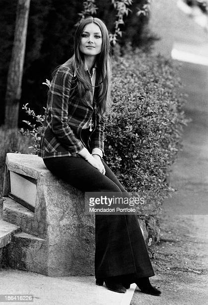 The German actress Barbara Bouchet an emerging face of the Italian comedy sits in a public park she wears a checkered pattern jacket and black pants...