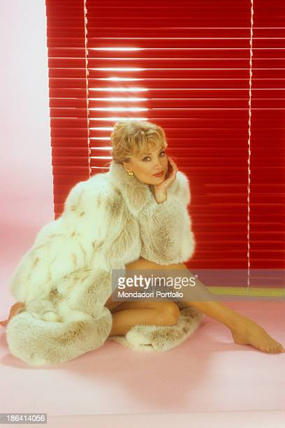 The German actress Barbara Bouchet born Gutscher and naturalized Italian seated on the floor into a photo studio before a red venetian blind she...