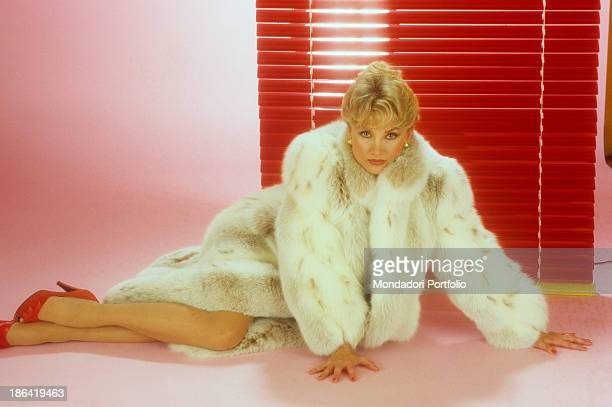 The German actress Barbara Bouchet born Gutscher and naturalized Italian lying on the floor near a red venetian blind into a photo studio the fashion...