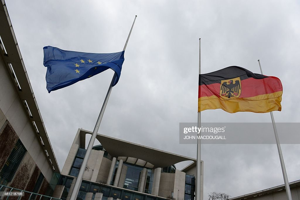 The German and the European flag fly at half mast outside the German Chancellery in Berlin on January 9 in commemoration of the victims of an...
