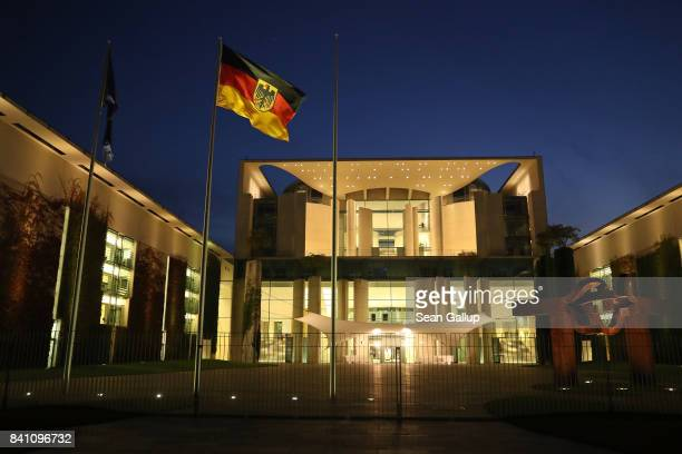 The German federal flag flies outside the Chancellery at twilight on August 30 2017 in Berlin Germany Germany is scheduled to hold federal elections...
