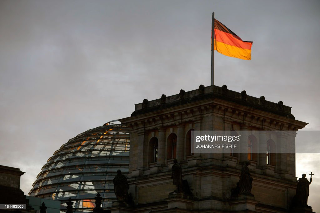 The German flag flys on the roof of the Reichstag, the building housing the German lower house of parliament during the 2nd round of exploratory talks on forming a coalition government with the Social Democratic Party (SPD) in Berlin on October 14, 2013. The exploratory talks with the left-leaning ecologist party are part of Merkel's hunt for a governing partner after her conservatives won September 22 elections but fell short of a ruling majority. AFP PHOTO / JOHANNES EISELE