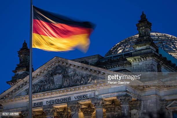 The german national flag blows in the wind on the Reichstag building on November 27 2016 in Berlin Germany