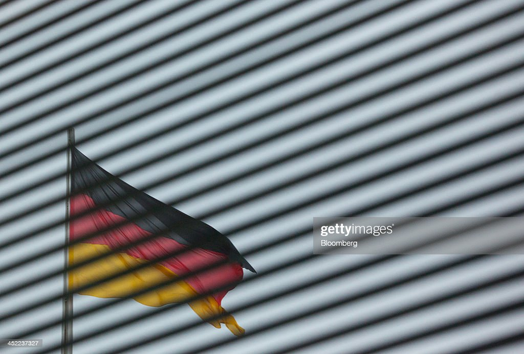 The German national flag flies at the German parliament building, or Reichstag, in Berlin, Germany, on Wednesday, Nov. 27, 2013. German Chancellor Angela Merkel reached an agreement with the Social Democrats on a coalition that would implement a national minimum wage and increase spending on pensions and infrastructure without raising taxes. Photographer: Krisztian Bocsi/Bloomberg via Getty Images