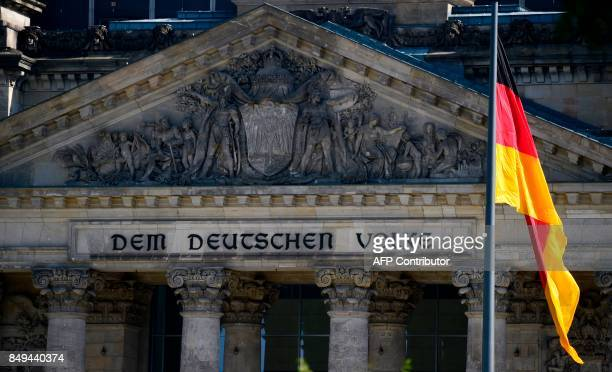 The German national flag is pictured next to the main entrance to the Reichstag building seat of the German lower house of Parliament Bundestag in...