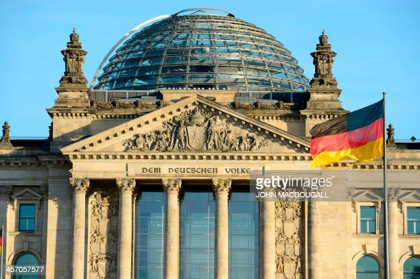 The German national flag is seen in front of the Reichstag building housing the German parliament Bundestag on December 16 2013 on the eve of the...