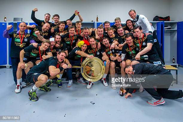 The German national handball team hold the trophy as they celebrate victory in the changing rooms after the Men's EHF Handball European Championship...