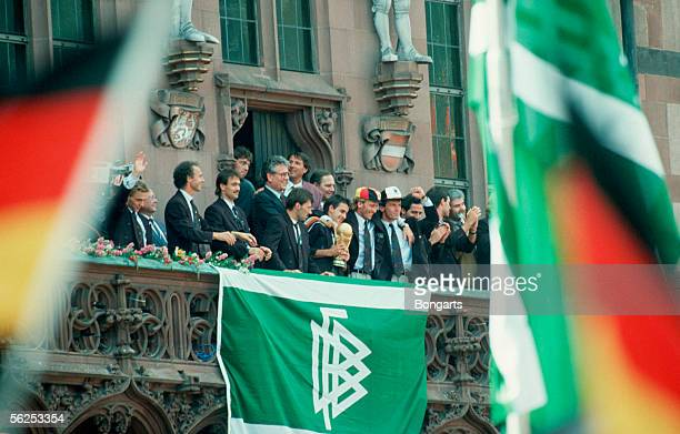 The German National Team celebrate with the World Cup Trophy after arriving at the guildhall of Frankfurt on July 9 1990 in Frankfurt Germany
