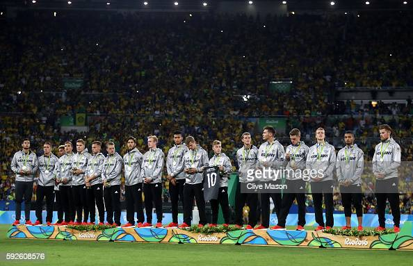 The German side line up to receive their silver medals following the Men's Football Final between Brazil and Germany at the Maracana Stadium on Day...
