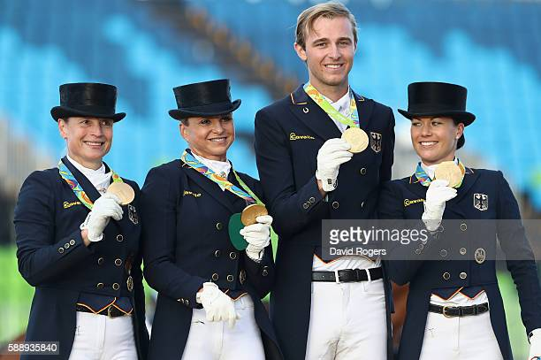 The German team of Isabell Werth Dorothee Schneider Sonke Rothenberger and Kristina BroringSprehe pose after winning the team gold during the final...
