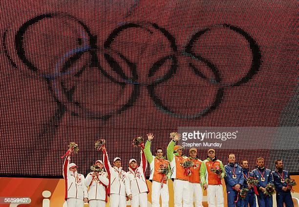 The German team of Ricco Gross Michael Roesch Sven Fischer and Michael Greis receive the Gold medal with The Russian Federation team of Ivan...