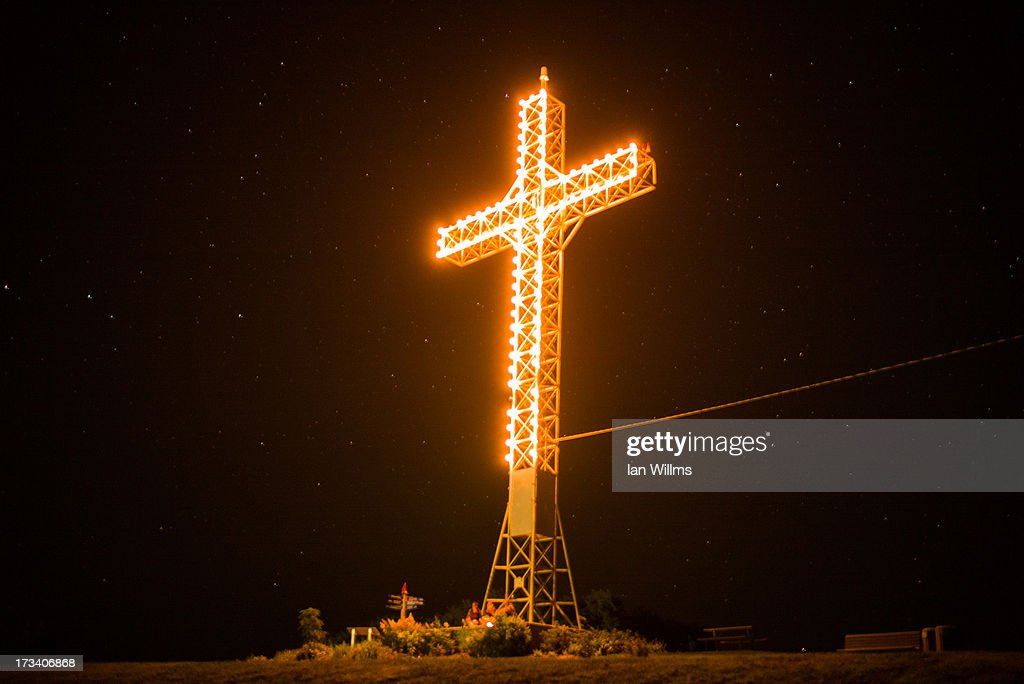 The giant illuminated cross that hangs over LacMegantic is seen July 13 2013 in LacMegantic Quebec Canada A train derailed and exploded into a...
