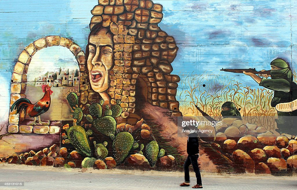 The giant mural painted by 25 Palestinian artists on the wall of Nablus Stadium, is seen on December 2, 2013 in the West Bank city of Nablus. The project, the 1,000-square-meter mural, dubbed 'Huna Canaan' ('Here is Canaan'), isn't just a painting. Rather, it's an illustration of more than 3,500 years of Palestinian history. The mural begins with a scene of a Canaanite woman working on the land. 'Canaan' is the oldest name associated with the land of Palestine. Other scenes portray the 'Nakba' (the dispossession of the Palestinians and concurrent establishment of Israel), the Intifada and the occupation of the holy city of Al-Quds (Jerusalem), along with a painting dedicated to late Palestinian leader Yasser Arafat. The mural ends with a painting in which Israel's notorious separation barrier is destroyed as a young Palestinian man passes through it while waving a Palestinian flag a reference to the end of the Israeli occupation and the establishment of an independent Palestine.