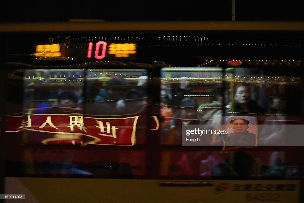 The giant portrait of the late chairman Mao Zedong reflects on the glass window of a bus in front of the Tiananmen Gate on March 1, 2013 in Beijing, China. The reshuffle will be completed at the first annual session of the 12th National People's Congress (NPC), which is scheduled to begin on March 5, and the first annual session of the 12th National Committee of the Chinese People's Political Consultative Conference (CPPCC), which will commence on March 3.