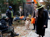 The Gibbs family of Clinton Hill Brooklyn stop at the Jane Bailey Memorial Garden to 'trick or treat' as Brooklyn residents participate in Halloween...