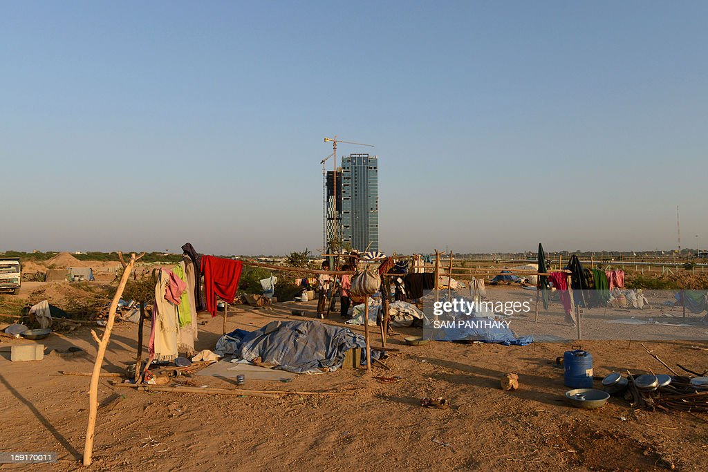 The GIFT City Tower 1 is seen past the makeshift dwellings of labourers during the eve of its inauguration in the outskirts of Gandhinagar, some 30 kms. from Ahmedabad, on January 9, 2013. The tower, the state's tallest building located in the Gujarat International Finance Tec-City (GIFT), will be officiated by India's Gujarat state Chief Minister Narendra Modi on January 10. AFP PHOTO / Sam PANTHAKY