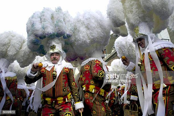 The Gilles hold oranges while parading with their ostrich feathers hats during the 'Gilles de Binche' traditional carnival parade through the streets...