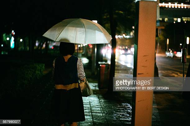 The girl holds an umbrella in the rain at night