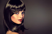 The girl in profile with black straight shiny hair and bangs . Model brunette with hairstyle of the care. Luxury fashion style, hair, cosmetics ,make-up