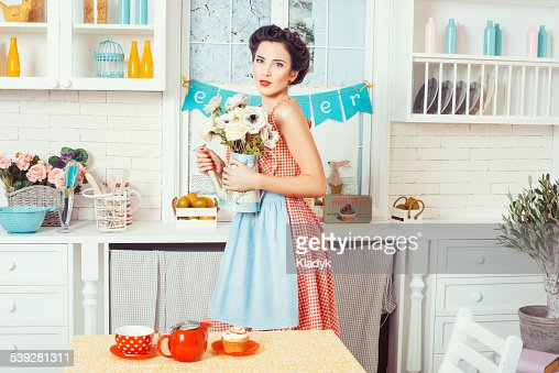 The Girl In The Kitchen With Flowers Stock Photo | Thinkstock