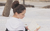 Cute girl with interest reading a book in the city Park.