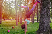girl is having exercise on a tree , recreation in a park , having props lying on a grass