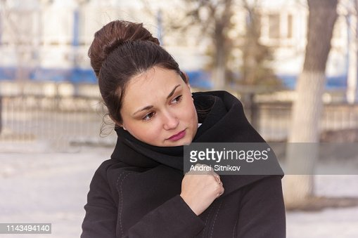 The girl is wrapped in a coat. : Stock Photo