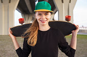 The girl looks at the camera. The skateboarder keeps a longboard on his shoulders and wearing a fashionable cap.