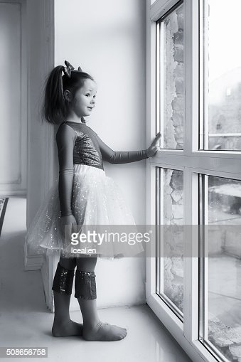 The girl standing at the window : Stock Photo
