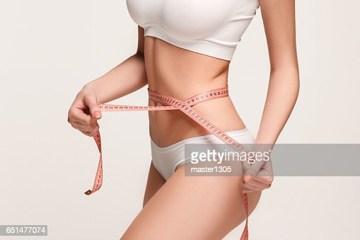 The girl taking measurements of her body, white background : Stock Photo