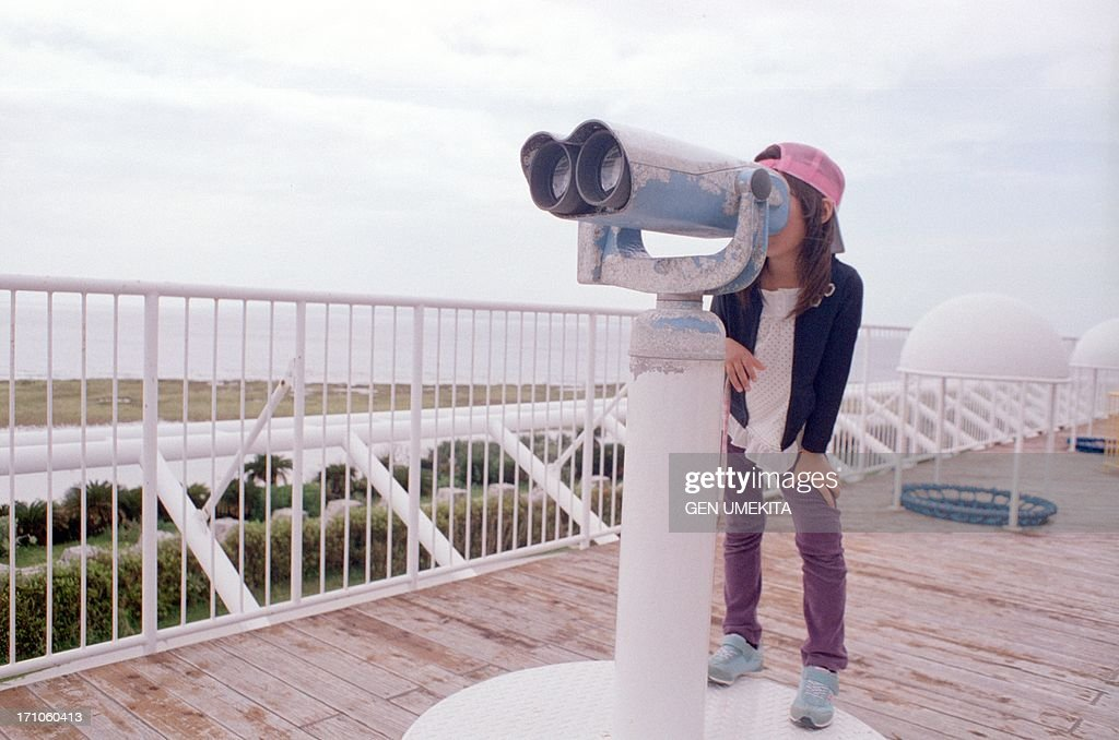 The girl who looks at a scene with binoculars