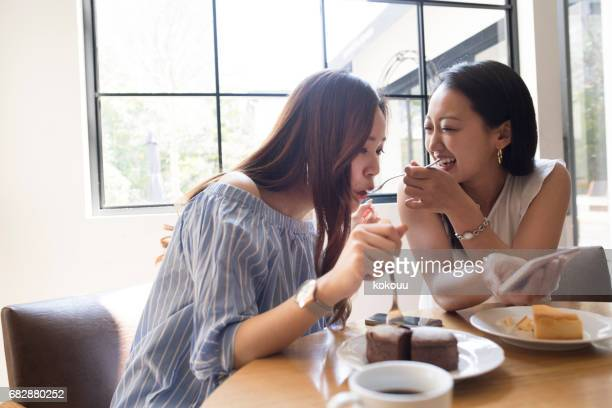 The girls eat cakes at the cafe.