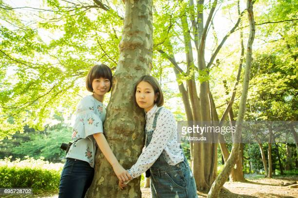 The girls hold hands with the trees