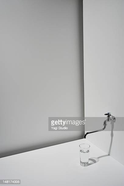 The glass which contains water, and faucet on whit