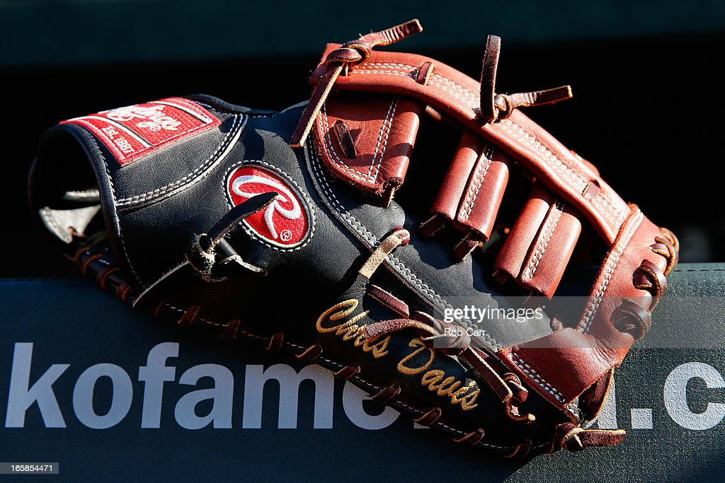 The glove of Chris Davis #19 of the Baltimore Orioles sits on the railing in the dugout before the start of the Orioles and Minnesota Twins game at Oriole Park at Camden Yards on April 6, 2013 in Baltimore, Maryland.