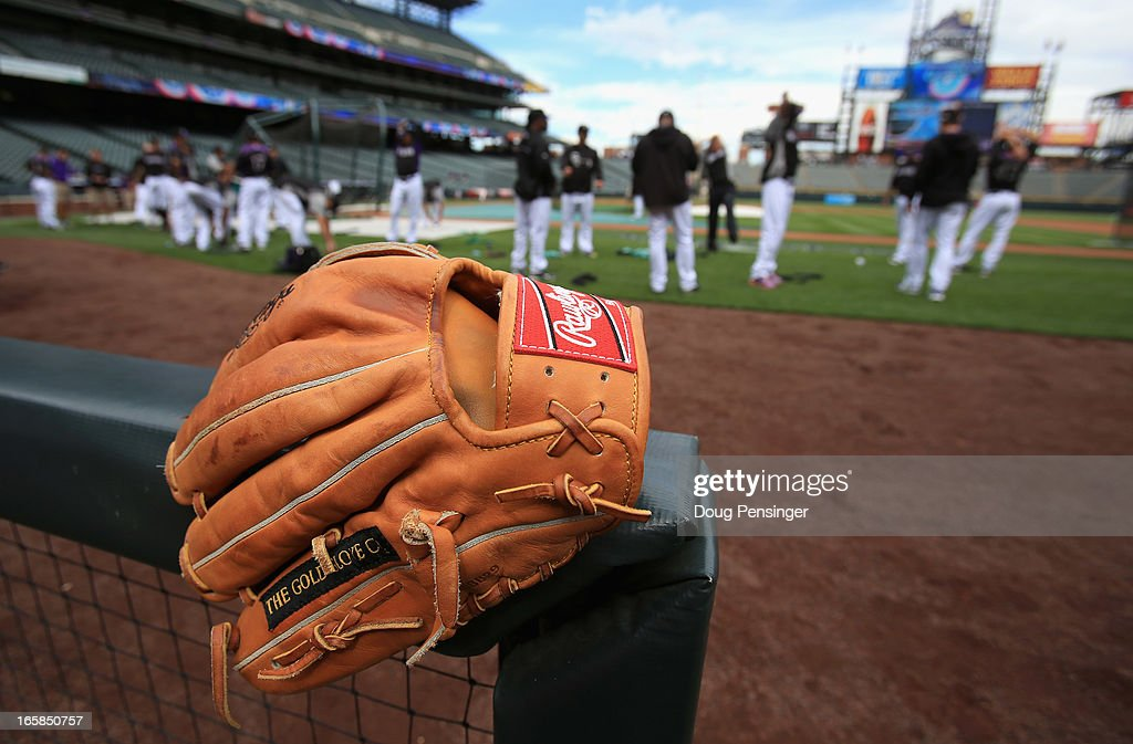 The glove of Reid Brignac of the Colorado Rockies is at the ready in the dugout as the Rockies prepare to face the San Diego Padres during Opening...