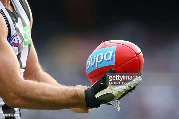 The glove of Travis Cloke of the Magpies holds the ball before a kick at goal during the round 14 AFL match between the Hawthorn Hawks and the...