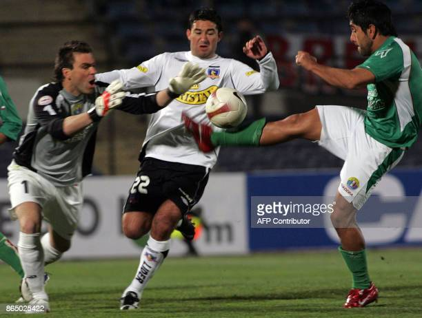 The goalie of Audax Italiano Víctor Loyola and his teammate Carlos Garrido struggle for the ball with Claudio Bieler from ColoColo during their Copa...