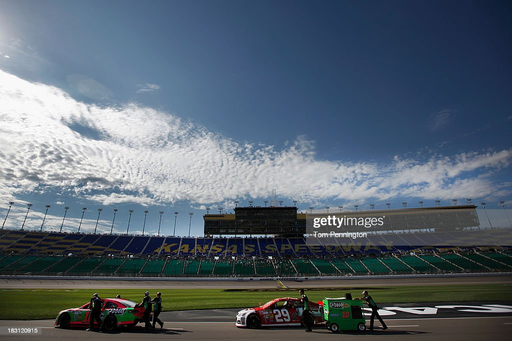 The #10 GoDaddy Chevrolet and the #29 Budweiser Chevrolet are pushed down the grid during qualifying for the NASCAR Sprint Cup Series 13th Annual Hollywood Casino 400 at Kansas Speedway on October 4, 2013 in Kansas City, Kansas.