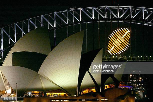 The Golden rugby ball logo of the Rugby World Cup 2003 hangs from the Sydney Harbour bridge and the Opera House 11 October 2003 in Sydney AFP PHOTO /...