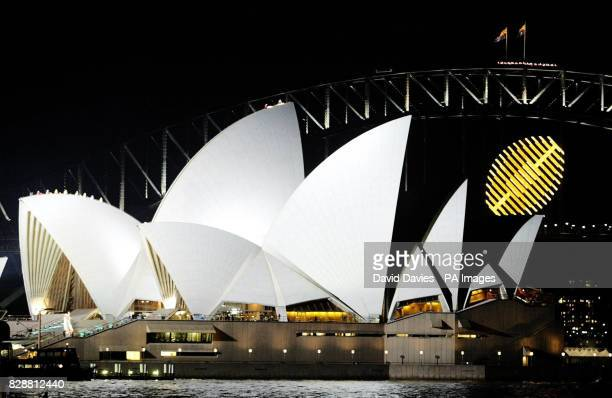 The golden rugby ball logo of this year's Rugby World Cup hangs from the Sydney Harbour Bridge beside the Opera House as final preparations are...