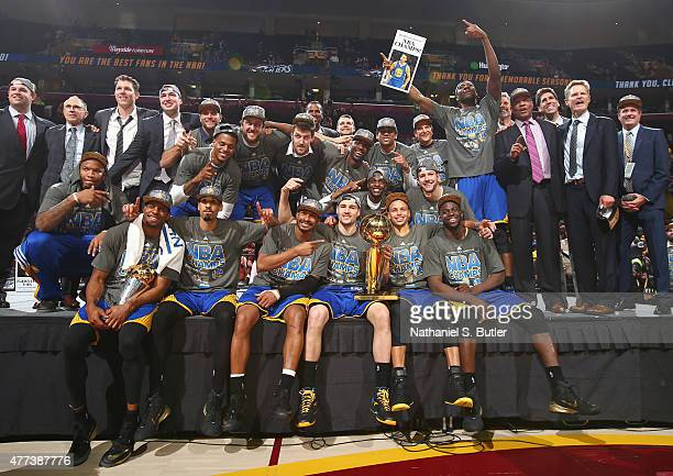 The Golden State Warriors smile while hugging the Larry O'Brien Championship Trophy after the Golden State Warriors win Game Six of the 2015 NBA...