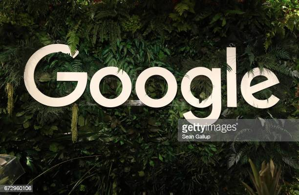 The Google logo hangs among plants at a juice stand at the W20 conference on April 25 2017 in Berlin Germany