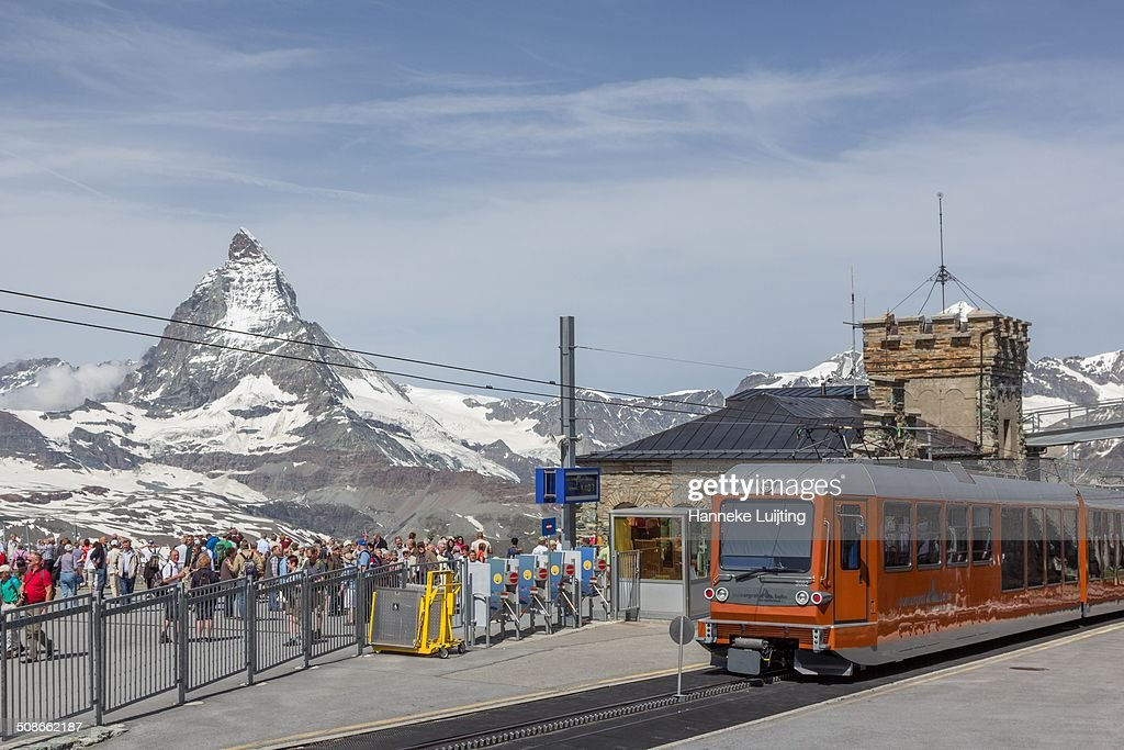 The Gornergrat Railway from Zermatt to Gornergrat (3089 m) in Switzerland. Tourists crowd the train station with the Matterhorn in the distance.